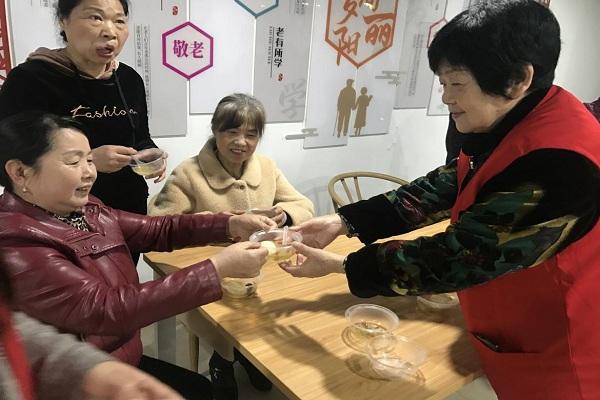 志愿者将煮鸡蛋送到参加活动的老人手上.jpg