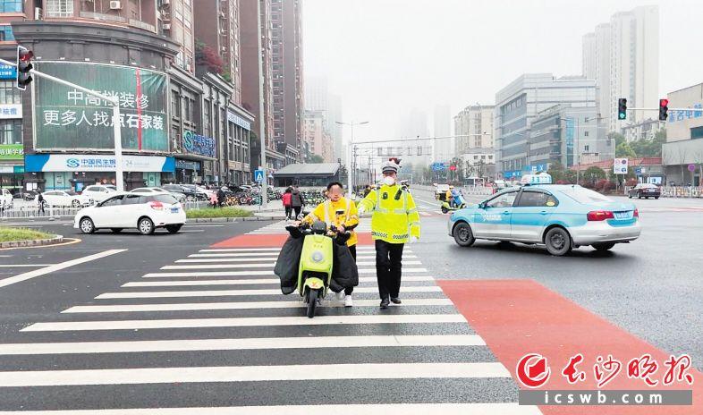 交警对一名未戴安全头盔的电动车骑行者进行劝诫。  龙雨泉供图
