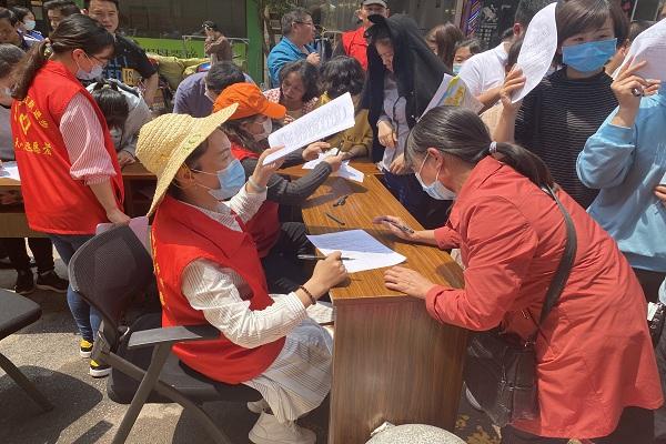 党员志愿者引导居民填写表格登记信息。.jpg