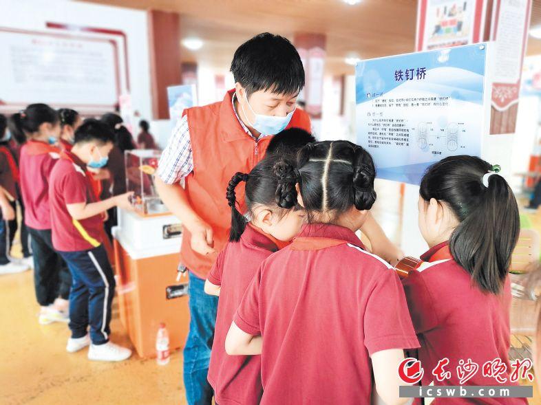 黄仁忠在科普大篷车进校园活动现场为孩子们演示讲解科技原理。  受访者供图