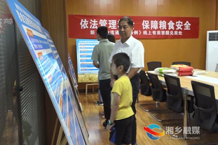 市民在宣传展板前驻足,学习《粮食流通管理条例》。.png