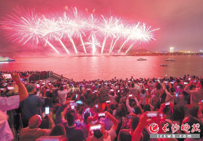 市民们在湘江东岸一起观赏橘子洲烟花秀。