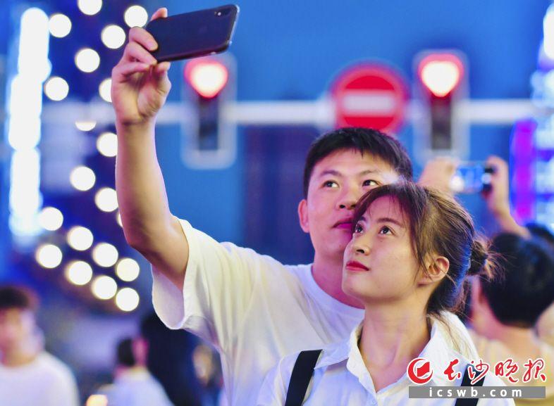 爱心红绿灯、粉红斑马线……这是一对情侣在爱心红绿灯前自拍打卡。
