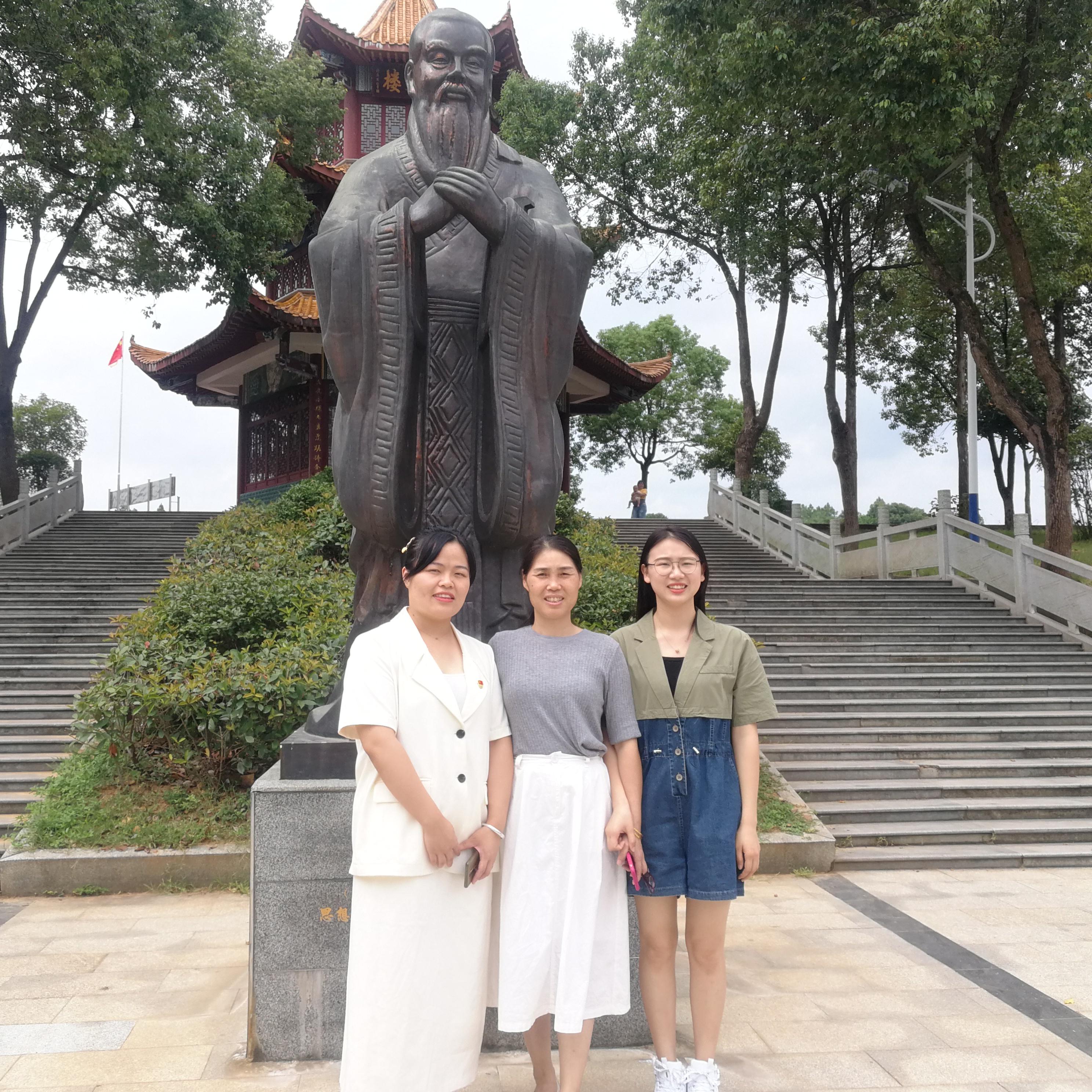 朱晖(中)现任学校初三年级组长,她十分关心年轻老师的成长。图为她在校园孔子雕像前与年轻老师在一起。 长沙晚报全媒体记者  黎铁桥摄