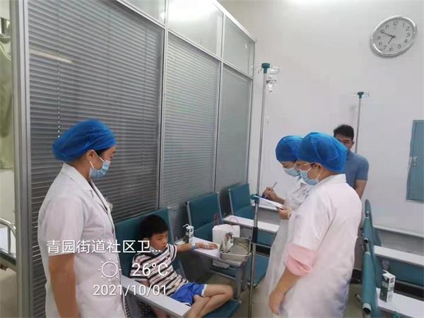 9青园街道社区卫生服务中心,一位做了扁桃体手术后的小朋友在中心输液留观,医护人员进行安抚。.jpg